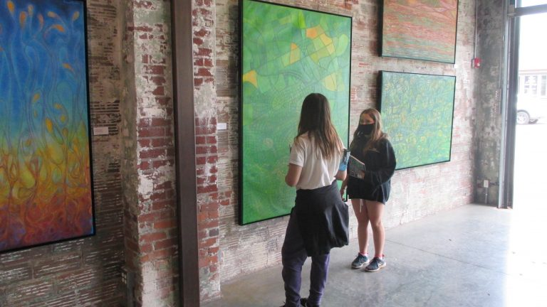 Category 5. 17. Two students from TPS discuss the paintings